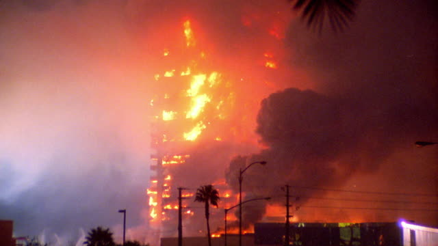 vidéos et rushes de wide shot dunes hotel/casino imploding and falling with smoke + fire / las vegas, nevada - imploding