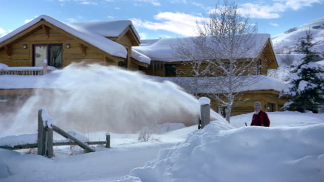 Wide shot elderly man snowblowing in front of country house / Jackson Hole, Wyoming