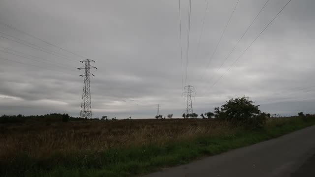 vidéos et rushes de wide shot electricity pylons stand in fields in a rural coastal area of cumbria uk on wednesday aug 14 power transmission lines run from electricity... - processus biologique