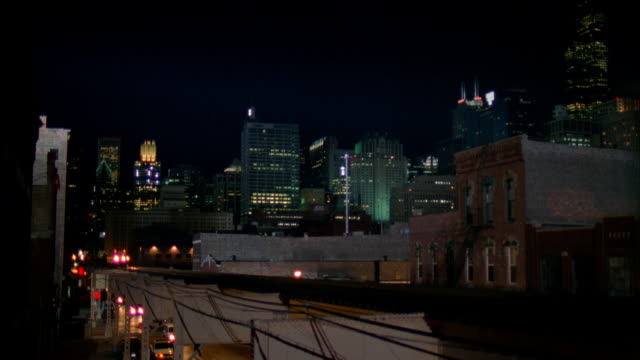 vídeos de stock, filmes e b-roll de wide shot elevated train traveling toward cam with skyline in background / dolly shot tilt down street below overpass / chicago - metrô de chicago