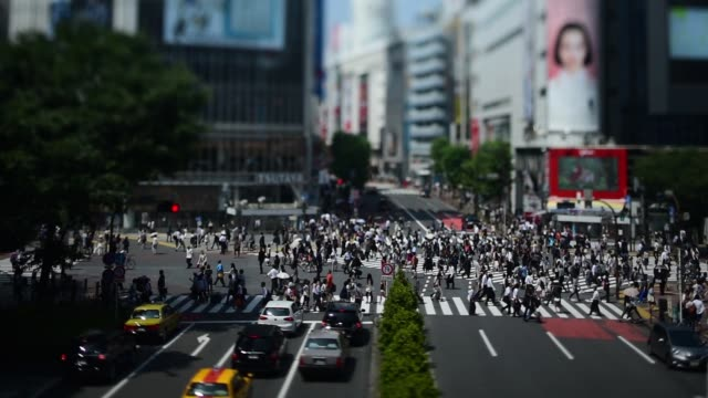 Wide shot elevated view of pedestrians crossing an intersection in the Shibuya district of Tokyo taken with a tiltshift lens