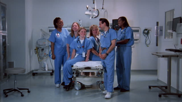 Wide shot emergency room staff wearing scrubs around gurney in ER