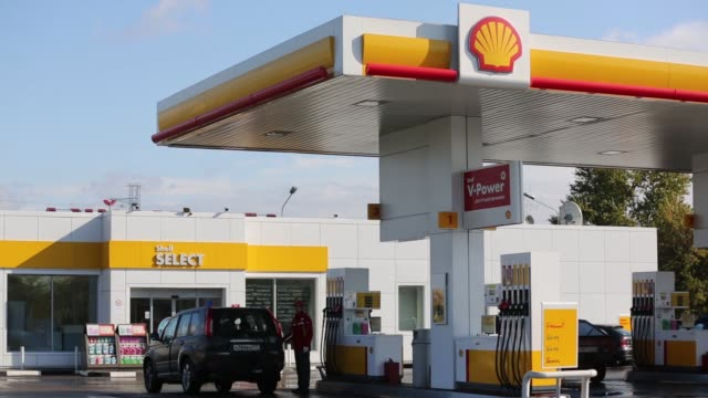 wide shot employees work on the forecourt of a shell gas station operated by royal dutch shell plc in moscow russia on tuesday sept 30 the shell logo... - ガソリンスタンド点の映像素材/bロール
