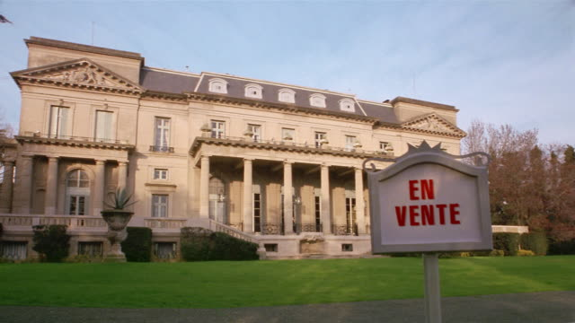 wide shot en vente (for sale) sign posted in front of mansion / argentina - colonna architettonica video stock e b–roll