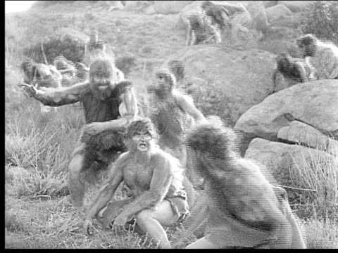 1914 b/w wide shot excited cavemen jumping on rocks - evolution stock-videos und b-roll-filmmaterial
