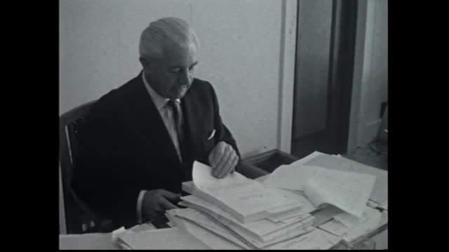 wide shot ext parliament house canberra 1950's/60s cars lined in front / close up ext / federal treasurer harold holt at desk with budget papers goes... - finanzministerium stock-videos und b-roll-filmmaterial