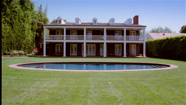 wide shot exteior rear view of mansion with swimming pool in backyard - establishing shot stock videos & royalty-free footage