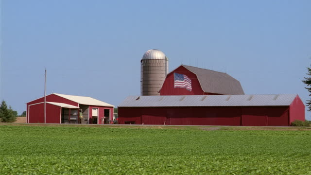 Wide shot exterior of barn with silo and American flag poster