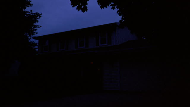 Wide shot exterior of house at night / lights in windows going out and coming on + going out again