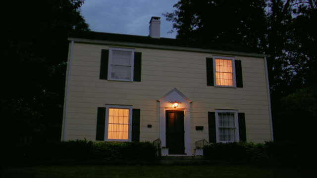 Wide shot exterior of house with porch light and lights in windows on