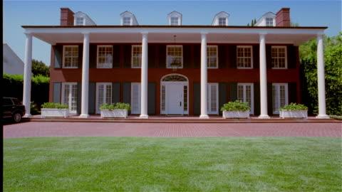 wide shot exterior of mansion with columns - establishing shot bildbanksvideor och videomaterial från bakom kulisserna