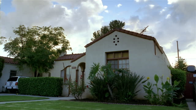 wide shot exterior of spanish-style house / man running out door / compton, california - mediterranean culture stock videos & royalty-free footage