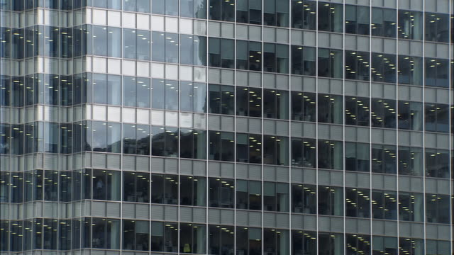wide shot exterior windows of modern office building/ pan corner of building with visible people in conference room/ london - ecke eines objekts stock-videos und b-roll-filmmaterial