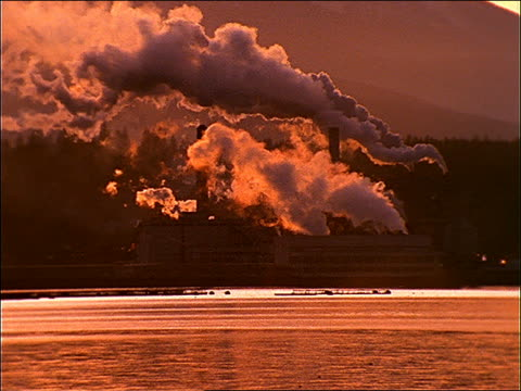 wide shot factory (paper mill) with thick smoke at sunset / water in foreground / port townsend, wa - pappersbruk bildbanksvideor och videomaterial från bakom kulisserna