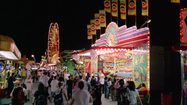 wide shot fairgoers strolling past stall at canadian national exhibition at night / toronto - kelly mason videos stock videos & royalty-free footage