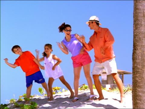Wide shot family dancing on beach / Miami, Florida