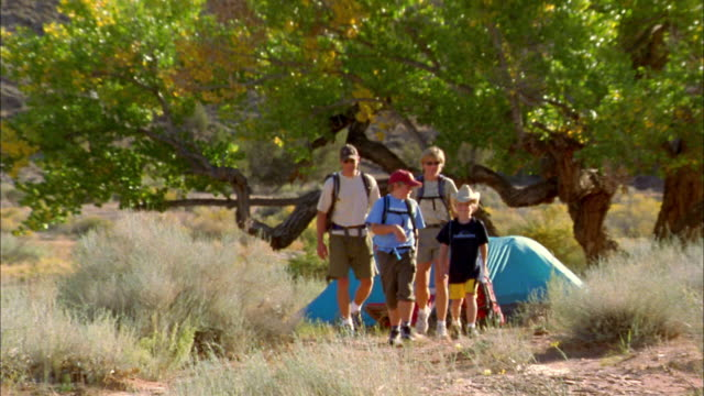 wide shot family hiking w/backpacks outdoors w/tent in background - camping stock videos and b-roll footage