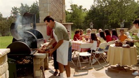 vídeos y material grabado en eventos de stock de wide shot family members attending barbecue in backyard / man smiling and presenting plate of meat to cam - cocido a la parrilla