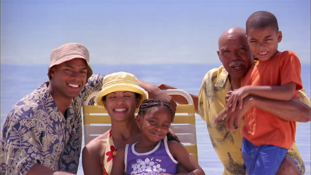 wide shot family posing around beach chair and smiling - 8 9 jahre stock-videos und b-roll-filmmaterial