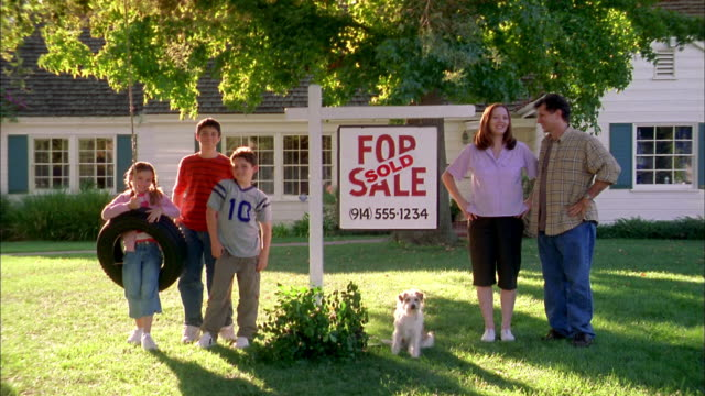 Wide shot family posing with'Sold' 'For Sale' sign in front yard of house