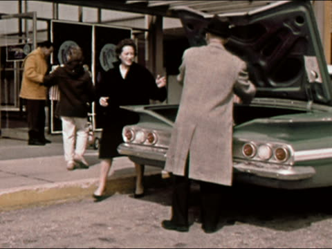 1964 Wide shot family removes Christmas packages from car on street / Long Island, New York / AUDIO