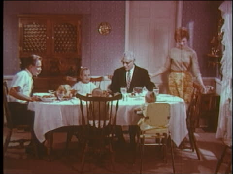 1960 wide shot family sitting down at dinner table + bow heads to say grace - 1960 stock videos & royalty-free footage