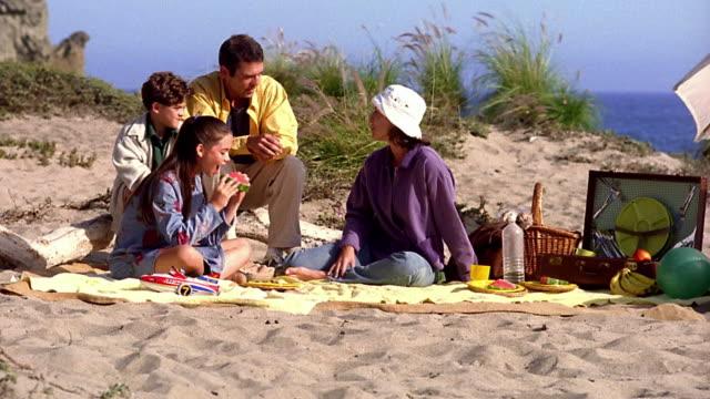 vídeos y material grabado en eventos de stock de wide shot family sitting on blanket on beach with girl eating watermelon / california - cesta de picnic