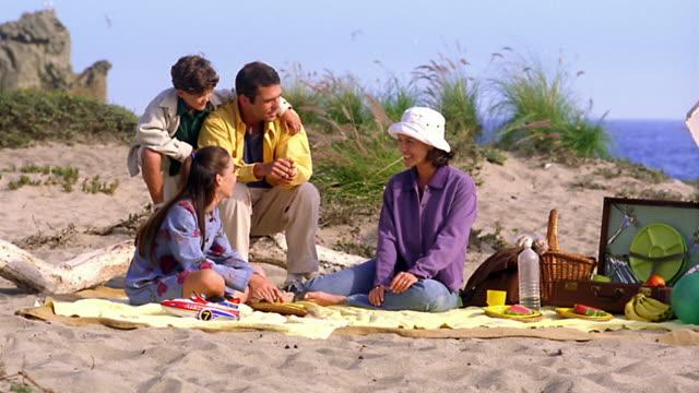 wide shot family sitting on blanket on beach with girl eating watermelon / california - ギフトバスケット点の映像素材/bロール