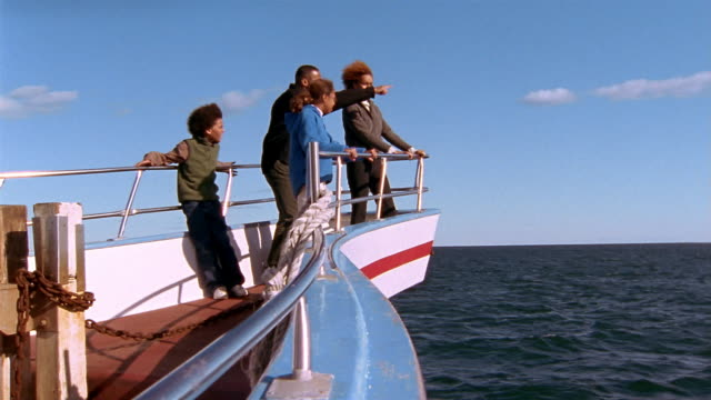 wide shot family standing on prow of boat looking out over water - whale watching stock videos & royalty-free footage