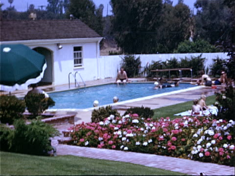 1952 wide shot family swimming in pool in landscaped backyard / beverly hills, california, usa  - beverly hills california stock-videos und b-roll-filmmaterial