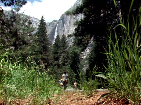 vídeos y material grabado en eventos de stock de 1999 wide shot family with four children riding bikes through yosemite national park/ california, usa - familia con cuatro hijos