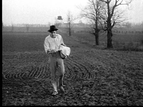 stockvideo's en b-roll-footage met 1909 b/w wide shot farmer sowing seeds in field by hand  - 1900 1909