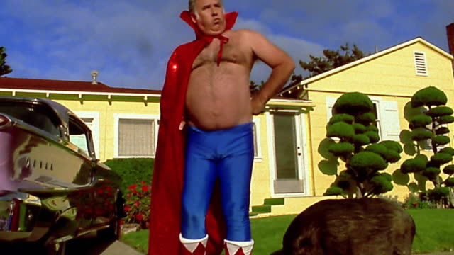 Wide shot fat mature man in superhero cape and tights running toward CAM past boar / low angle close up flexing muscles