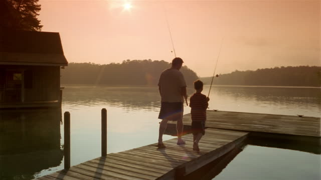 wide shot father and son carrying fishing poles to end of dock / clarkesville, georgia - clarkesville stock videos & royalty-free footage