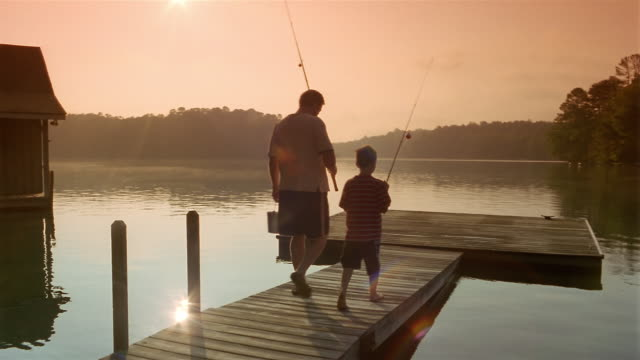 Wide shot father and son carrying fishing poles to end of dock / Clarkesville, Georgia