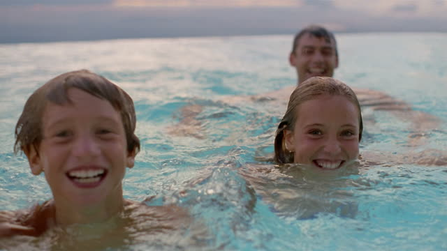 wide shot father and two children swimming toward cam in infinity pool / close up smiling at cam / south africa - pool mit gegenströmung stock-videos und b-roll-filmmaterial