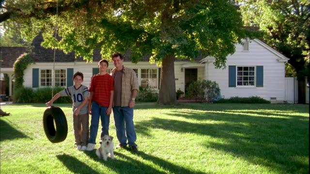 vidéos et rushes de wide shot father and two sons posing in yard w/dog + tire swing - balançoire pneu