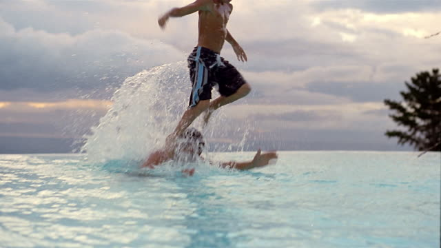 vídeos de stock, filmes e b-roll de wide shot father lifting son off shoulders and throwing into water in swimming pool / south africa - lago infinito