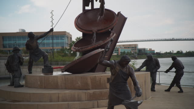 Wide shot featuring the five manufacturing foundry workers in the tribute to labor sculpture along the Missouri River, titled 'Labor' by Matthew Placeck.
