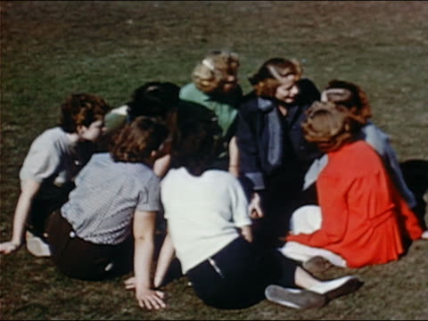 vidéos et rushes de 1953 wide shot female high school student joining group sitting on lawn and gossiping - 16 17 ans