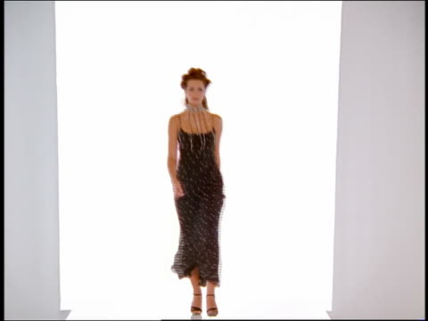 Wide shot female Hispanic model in long dress walking on catwalk and laughing