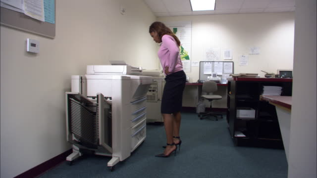 Wide shot female officer worker waiting for photocopier to work / kicking and pounding photocopier / low angle