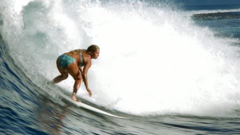 vídeos y material grabado en eventos de stock de wide shot female surfer paddling, standing on surfboard and riding wave / tahiti - surf