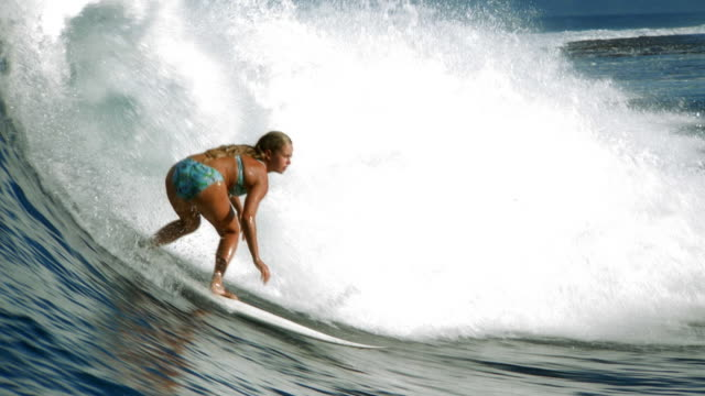 vídeos de stock, filmes e b-roll de wide shot female surfer paddling, standing on surfboard and riding wave / tahiti - surfe