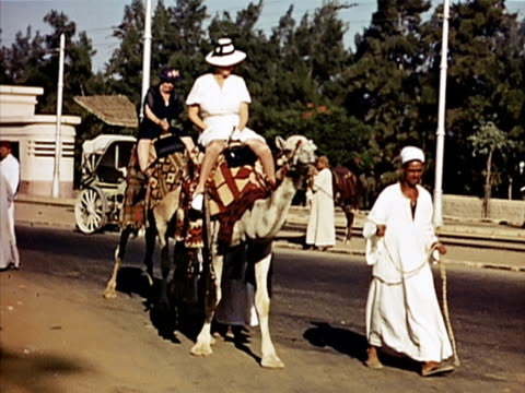 1939 Wide shot female tourists riding camels/ Cairo