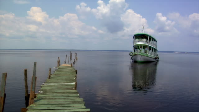 vídeos de stock e filmes b-roll de wide shot ferry approaching pier / rio negro, brazil - barco de turismo