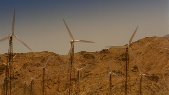 wide shot field of wind turbines spinning - mellanstor grupp av objekt bildbanksvideor och videomaterial från bakom kulisserna