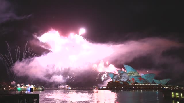Wide Shot fireworks explode as projections are displayed on the Sydney Opera House during the International Fleet Review on October 5 2013 in Sydney...