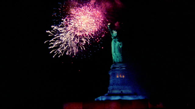 Wide shot fireworks exploding around Statue of Liberty at night / New York City