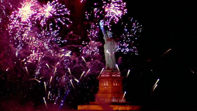 Wide shot fireworks exploding around Statue of Liberty at night / New York